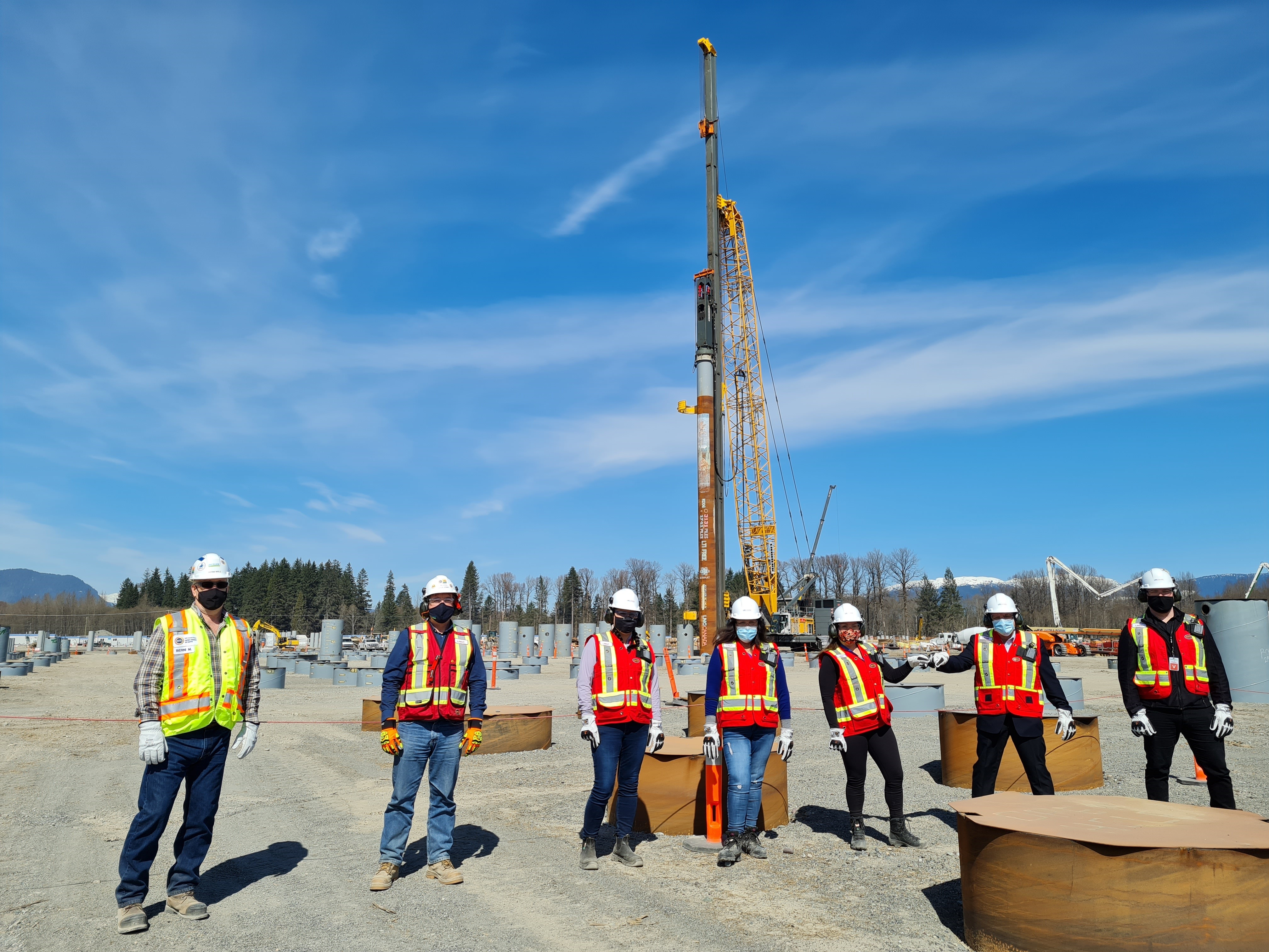 Workers in front of the last pile at the LNG Canada site in Kitimat, B.C.